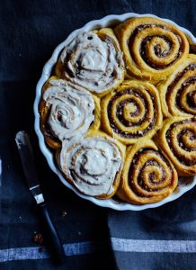 Sweet Potato Cinnamon Rolls Recipe by The Wood and Spoon Blog by kate Wood. These are fluffy, light cinnamon rolls and that make several pans or just a few large oversized big cinnamon rolls. These contain sweet potato puree or you can use pumpkin puree from a can. Filled with a cinnamon and brown sugar pecan filling and topped with a simple and easy cream cheese frosting / icing / glaze. Make these ahead if desired. Find the recipe for these fall favorite best breakfast buns at thewoodandspoon.com