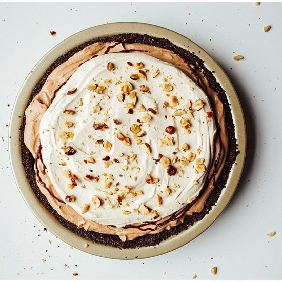 Hazelnut Mocha Cream Pie is a simple, almost no bake pie make with a chocolate cookie crust, and a Nutella cream cheese and whipped cream filling. This is a chocolate lover dessert topped with extra fluffy stiff peak whipped cream and crunchy toasted nuts / hazelnuts. The pie is a great make ahead dessert to feed a crowd. Icebox pie, icebox cake, no bake pie, easy, simple summer recipe by thewoodandspoon.com