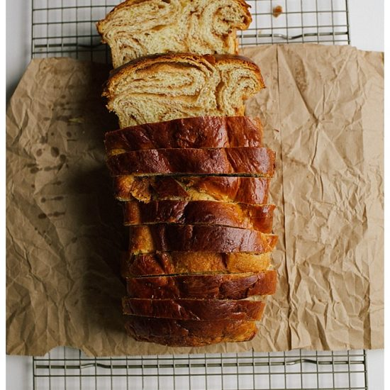 Cinnamon Swirl Bread Recipe by the Wood and Spoon blog by Kate Wood. This recipe makes two loaves of cinnamon babka or brioche style bread using butter and eggs. The bread is soft and sweet like Hawaiian bread but makes homemade bread similar to commercial breakfast bread. There is a tutorial on how to roll these fluffy loaves and how to get lots of swirls throughout. Find the recipe on thewoodandspoon.com