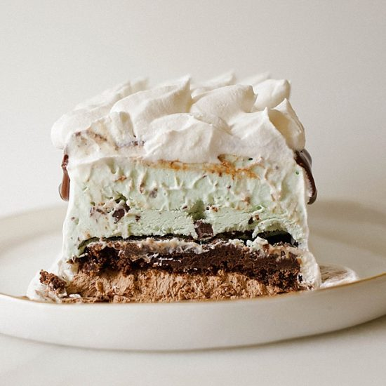 Mint Brownie Ice Cream Cake recipe by The Wood and Spoon Blog by Kate Wood. A make ahead no churn ice cream cake recipe. Filled with chocolate ice cream made from cocoa powder, and a mint chocolate chip ice cream. Simple and quick brownie recipe on the inside and hot fudge chocolate sauce. You can adapt this recipe to be semi-homemade and you can make ahead this loaf pan cake in advance to serve a crowd. Great summer frozen dessert idea, coated in cool whip or whipped cream. Add chocolate cookies or Oreos if you want! Thewoodandspoon.com