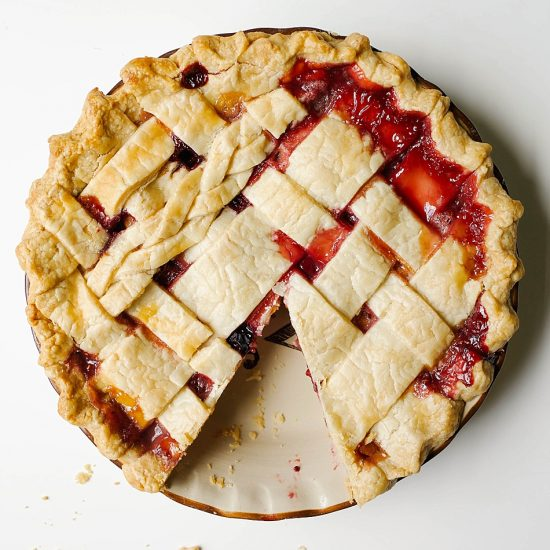 Peach Berry Pie Recipe by The Wood and Spoon Blog. A flaky, butter double crust pie dough filled with sliced peaches, straberries, raspberries, blueberries, and more. This is a perfect make ahead summer dessert and the simple instructions make this an easy pie to share with a crowd. Decorate the top of the pie with a lattice if desired. Bring this mixed berry and peach pie to your next party, BBQ, or outdoor event. woodandspoon.com