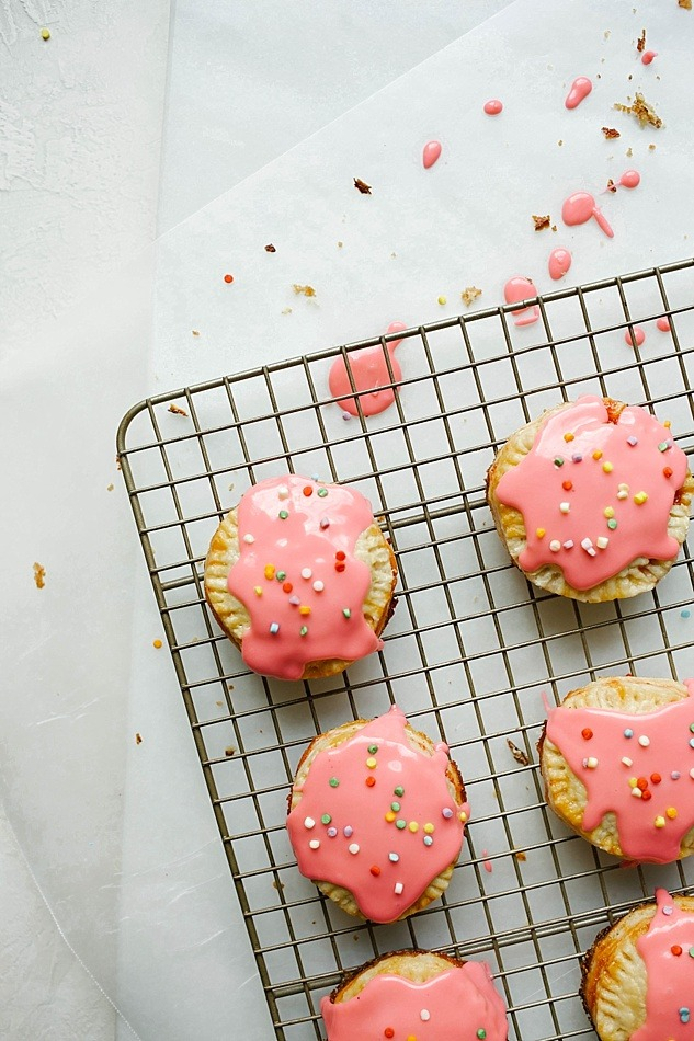 Strawberry Fig Pop-Tarts Recipe by The Wood and Spoon Blog by Kate Wood. This recipe is for mini round pop tarts make of butter pie crust pasty and simple homemade strawberry fig preserves. Top with an easy confectioner's sugar icing glaze and sprinkles for a fun breakfast or dessert. Find the recipe for the jam and these simple mini hand pie pastries on thewoodandspoon.com