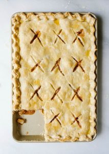 """Caramel Apple Slab Pie Recipe by The Wood and Spoon Blog by Kate Wood. This is a pie recipe prepared in a jelly roll pan, quarter sheet pan, or a 9""""x 13"""" pan. Filled with tart autumn apples and a salted caramel sauce inspired by bobby flay, fall dessert is perfect for serving a crowd and can easily be made ahead. Find the details and how to make your own Thanksgiving inspired treat on thewoodandspoon.com"""