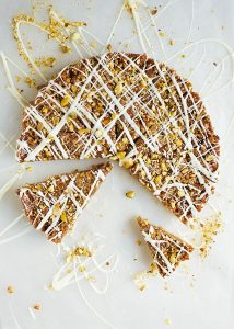 Pistachio Honey Bars Recipe by The Wood and Spoon Blog by Kate Wood. These are a simple, press in lemon shortbread crust topped with a gooey nutty filling. Walnuts, pistachios, honey and brown sugar make up these bars which are also spiced with cinnamon and cardamom - just like baklava! The recipe is simple, make ahead, and a sweet Southern take on the middle eastern / Greek classic. Drizzle with a white chocolate topping, for a fancy take on these easy cookies. Find out how to bake them and more on the recipe on thewoodandspoon.com