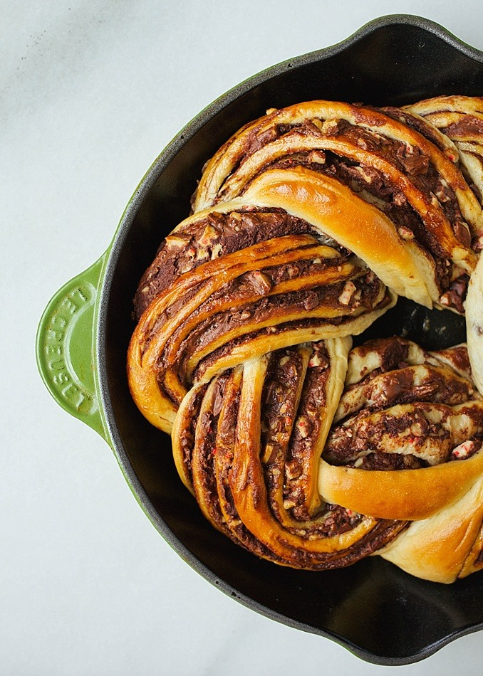 Peppermint Bark Bread Recipe by Kate Wood of The Wood and Spoon blog. This is a sweet yeast bread similar to babka filled with a semisweet chocolate filling and bits of chopped white chocolate peppermint bark. The bread is swirled and braided into a wreath and baked in a cast iron skillet. This bread is festive enough for dessert but able to be eaten as breakfast too. Find the tutorial for how to braid bread and a review of the wolf gourmet counter oven on thewoodandspoon.com Christmas holiday recipe!