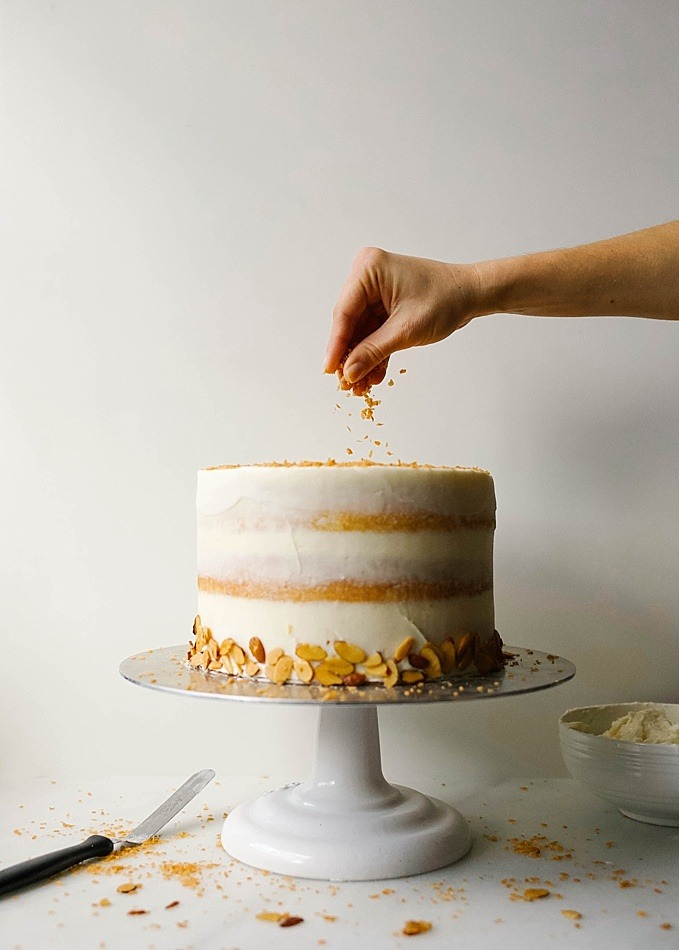Almond Coconut Cake recipe by Wood and Spoon Blog by Kate Wood. This is a recipe for a sweet and fluffy almond layer cake, speckled with flakes of sweetened coconut and frosted with a coconut American buttercream. The whole thing is topped with extra toasted coconut and almond, a cake that is as beautiful as it is delicious. This layer cake is simple and easy to make, and learning how to make stacked naked cakes is fun! Find the recipe for this Easter / spring cake on thewoodandspoon.com