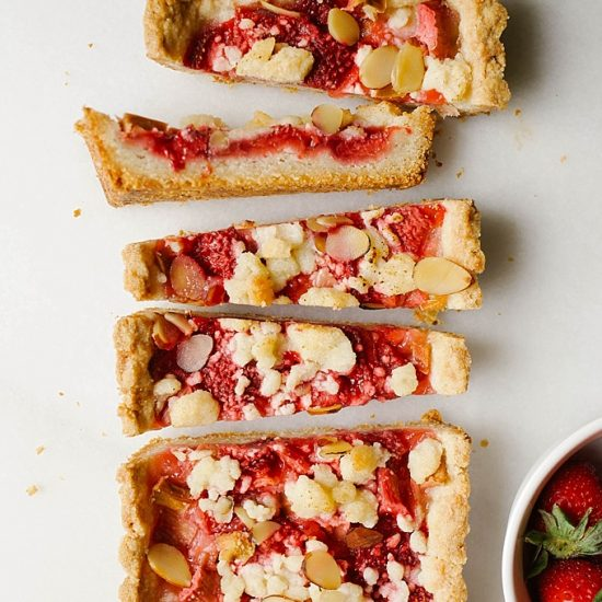 Berry Rhubarb Tart by Wood and Spoon blog. This is an almond shortbread crust tart filled with fresh strawberries and rhubarb. The remaining crust is crumbled on top of this elegant simple tart along with sliced almonds. This is a pretty dessert to make in the summer and spring and is perfect for ladies' tea or Mother's Day! Find the recipe for this pastry at thewoodandspoon.com by Kate Wood