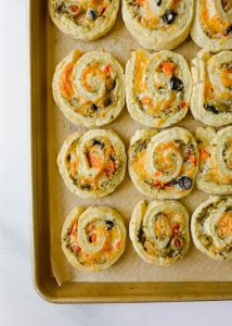 Tomato Olive Rolls by Wood and Spoon blog. These are scone like pinwheels with basil pesto, green and black olives, mozzarella and asiago cheese, and tomatoes! All of the ingredients are wrapped up in the butter and cream dough and baked until the cheese and crust are golden brown. These are similar to appetizers you can make with crescent rolls! Find the recipe and how to for these Italian mediterranean party snack foods on thewoodandspoon.com