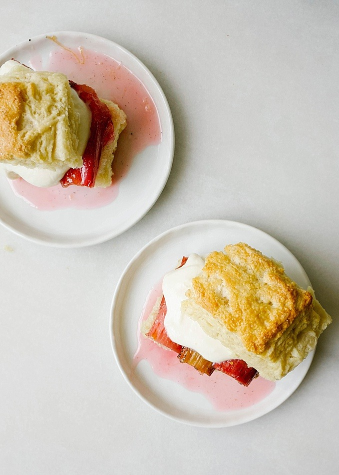 Rhubarb Shortcakes by The Wood and Spoon blog. These are scone like biscuits topped with a roasted rhubarb and vanilla bean and whipped mascarpone cream. The cakes are tender and layered and flaky, while the fruit is sweet and tangy. This is a great way to use up rhubarb and is a great summer dessert for a party. Read more about the recipe and how to on thewoodandspoon.com