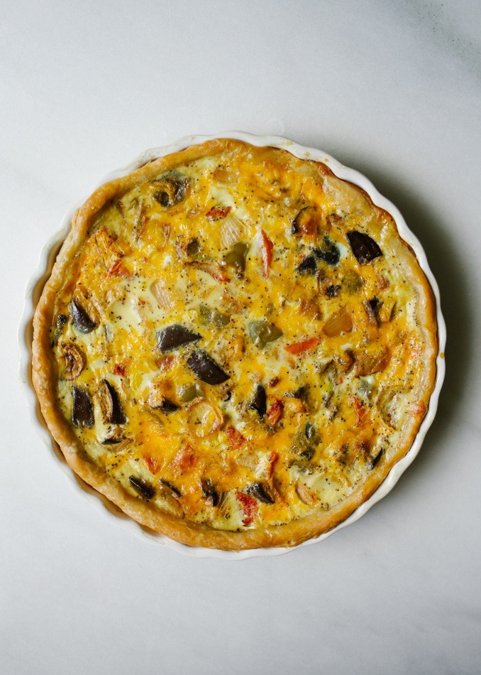 Roasted Summer Vegetable Quiche by Wood and Spoon blog. This is an all-butter pie crust filled with a cheesy quiche! Milk, parmesan, and cheddar are the dairy and fresh cooked vegetables and herbs are the filling. What to do with leftover vegetables and meat? Chop it and bake into this wonderful quiche! Sausage, chicken, bacon, or other vegetables would be a welcome addition for this dish that is great for breakfast, brunch, lunch or dinner. Find the recipe and how to on thewoodandspoon.com by Kate Wood. recipe