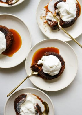 Molton Caramel Chocolate Cakes by Wood and Spoon. These are rich dark chocolate Lava cakes with a homemade salted caramel sauce in the center. Each individual dessert prepared in ramekins are baked until the gooey centers are melted and the cake is baked. Each treat is served with fresh whipped cream. Find the recipe and learn more about this fancy decadent dinner party finisher at thewoodandspoon.com by Kate Wood