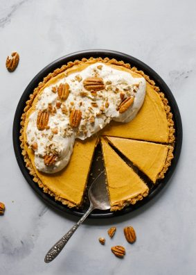Pumpkin Pecan Tart with Maple Whipped Cream by Wood and Spoon. This is a graham cracker and pecan salted crust baked and filled with a no bake pumpkin cream cheese filling. Flavored with brown sugar and cinnamon, this pie is cool but totally fall. Top the whole thing off with toasty pecans and maple whipped cream. Give this autumn dessert a try for Thanksgiving or upcoming dinner parties! Recipe by Kate wood on thewoodandspoon.com