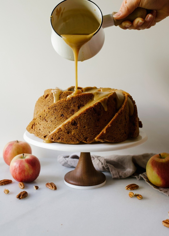 Brown Sugar Apple Bundt Cake recipe by Wood and Spoon blog. This is a fresh apple bundt cake with chunks of apples and pecans and a thick, brown sugar glaze. The cake bakes tall in a bundt or fluted pan and is topped with an old fashioned almost caramel like icing. This is a great cake to serve as dessert or breakfast this fall and at upcoming holidays. Find the recipe on thewoodandspoon.com by Kate Wood.