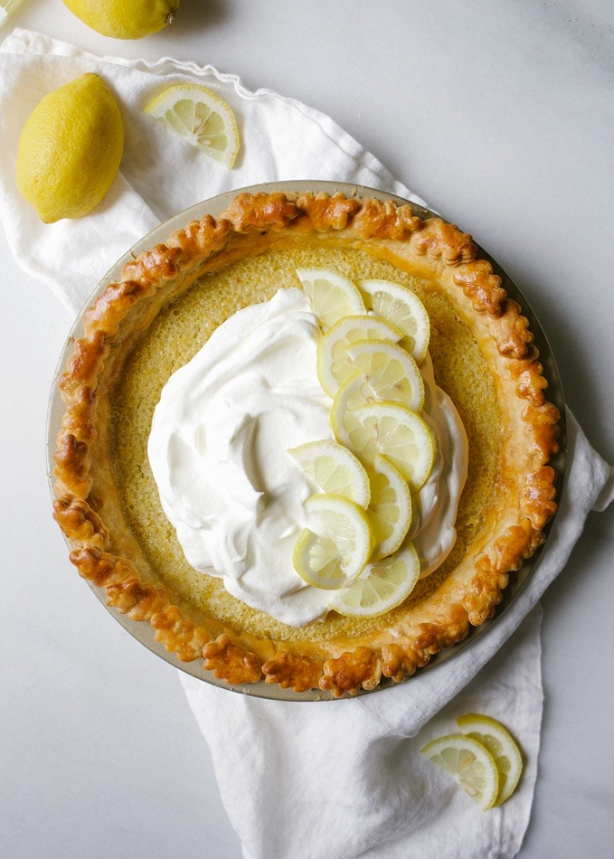 Lemon Olive Oil Pie Recipe by wood and spoon blog. This is a lemon zest and juice filled chess pie made with and olive oil pie crust. The flavor of the Lucini olive oil comes out subtly and perfumes this pie. The crust crisps nicely and the filled stays gooey and sweet like a lemon bar. Finish the pie off with freshly whipped cream. Read more about the recipe on thewoodandspoon.com