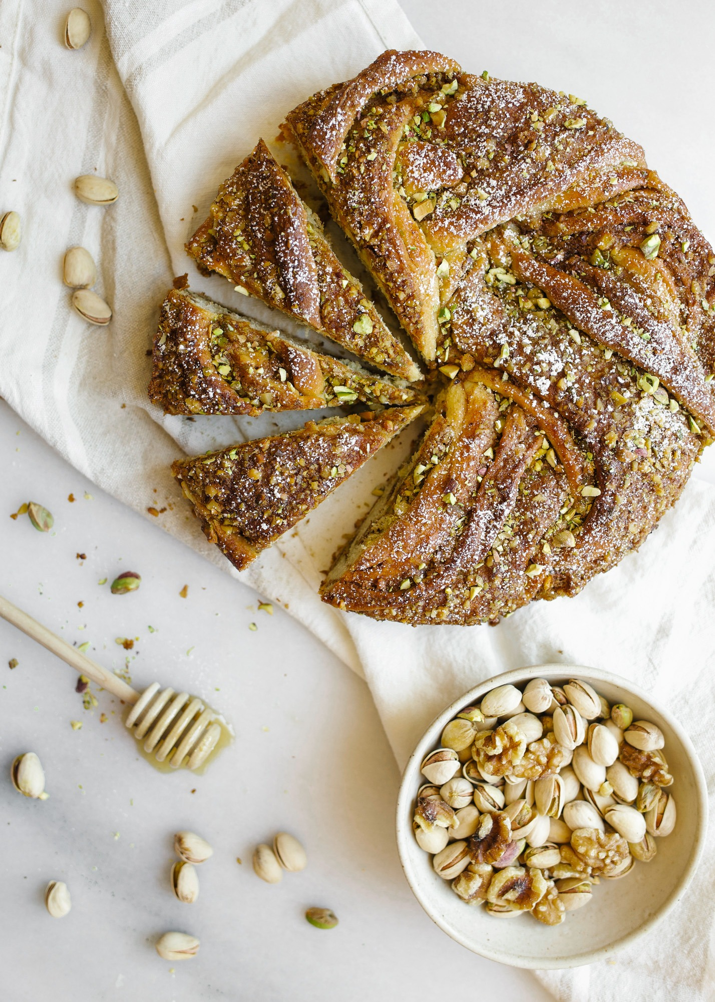 Braided Baklava Brioche by Wood and Spoon. This is a wreath loaf inspired by the meditteranean dessert filled with cinnamon, honey, walnuts, and pistachios. The yeast dough is sweetened with brown sugar and honey syrup and the crunchy nut filling adds flavor and texture. Heat up warm slices as a dessert or for breakfast. Learn more and how to braid the bread on thewoodandspoon.com
