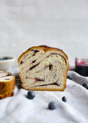 Blueberry Babka recipe by Wood and Spoon. This is a butter filled braided yeast loaf filled with a blueberry lemon and cinnamon swirl jam. The loaves are twisted and bake into wonderful toasting bread. Find the recipe for this fresh summer baked good on thewoodandspoon.com by Kate Wood