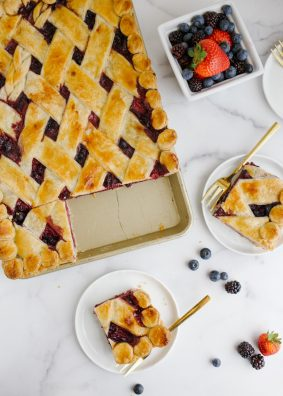 Berry Slab Pie by Wood and Spoon Blog. This is a triple berry pie with blueberries raspberries and strawberries, scented with cinnamon and layered flat in a sheet pan. This summer pie serves a crowd and has an all-butter pie crust. This make ahead dessert is great for outdoor parties and picnics. Learn how to make this lattice on thewoodandspoon.com