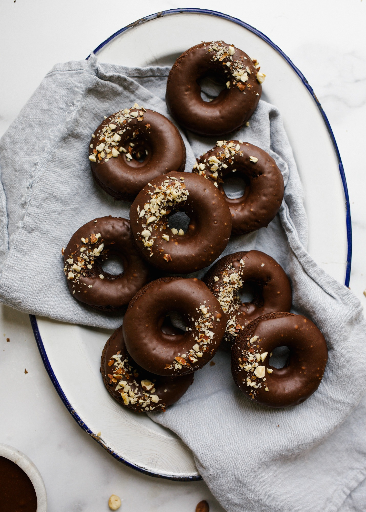 Chocolate Hazelnut Doughnuts by Wood and Spoon blog. These are baked dark chocolate cocoa powder donuts makes with melted butter and topped with a chocolate hazelnut glaze. Sprinkled nuts on top beauty up these quick breakfast pastries that can be made in one bowl! Read more about the recipe on thewoodandspoon.com.