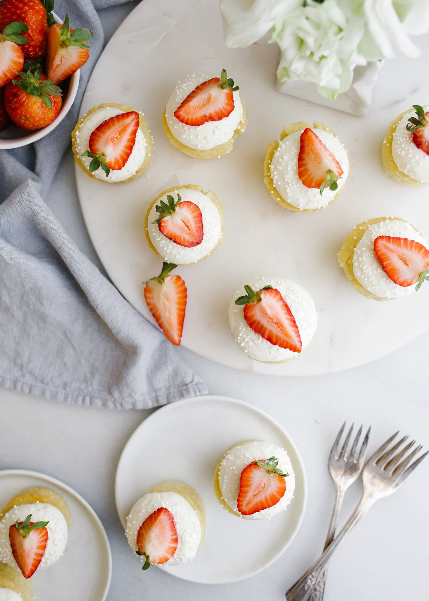 Mini Victoria Cakes by Wood and Spoon. These are mini sponge cupcakes with a strawberry jam filling and whipped cream topping. These are fancy looking little two bite treats perfect for tea parties. Read all about these cute summer desserts on thewoodandspoon.com