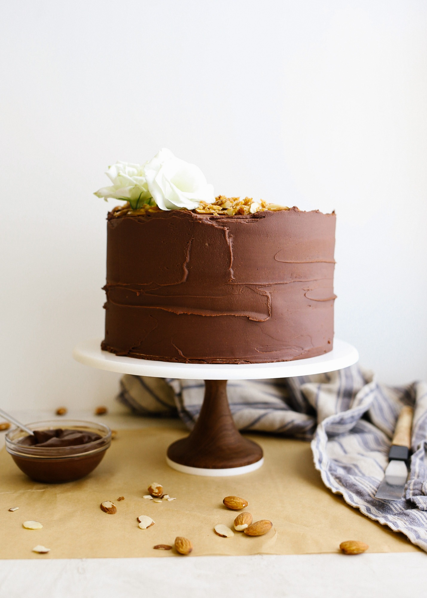 Almond Toffee Cake by Wood and Spoon. This is a vanilla layer cake with a rich chocolate fudge frosting and bits of homemade almond roca toffee throughout. The layer cake has a sweet and salty flavor and is rich with the addition of real chocolate buttercream. learn how to make this caramel tasting stacked celebration cake on thewoodandspoon.com
