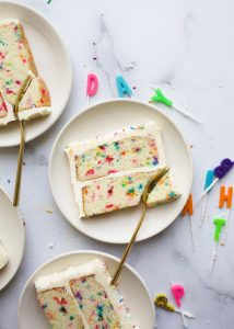 Funfetti Cake by wood and Spoon blog. This is a sprinkle birthday cake that tastes like the boxed cake mix! Features a clear vanilla extract American buttercream made with cream cheese and loaded of colorful rainbow sprinkles. Learn how to make this cake at home with real ingredients for celebrations and kids birthdays on thewoodandspoon.com