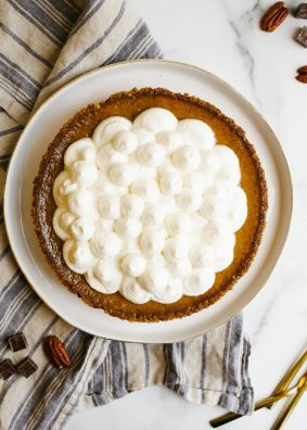 Black Bottom Pumpkin Pie is a creamy baked fall custard pie with a fudge chocolate bottom and pecan pie crust ready made from Diamond nuts. Topped with whipped cream and chocolate shavings this is a great holiday / Thanksgiving alternative for chocolate lovers. This pie is a simple one to make and bakes up without cracks! Learn more about the recipe on thewoodandspoon.com
