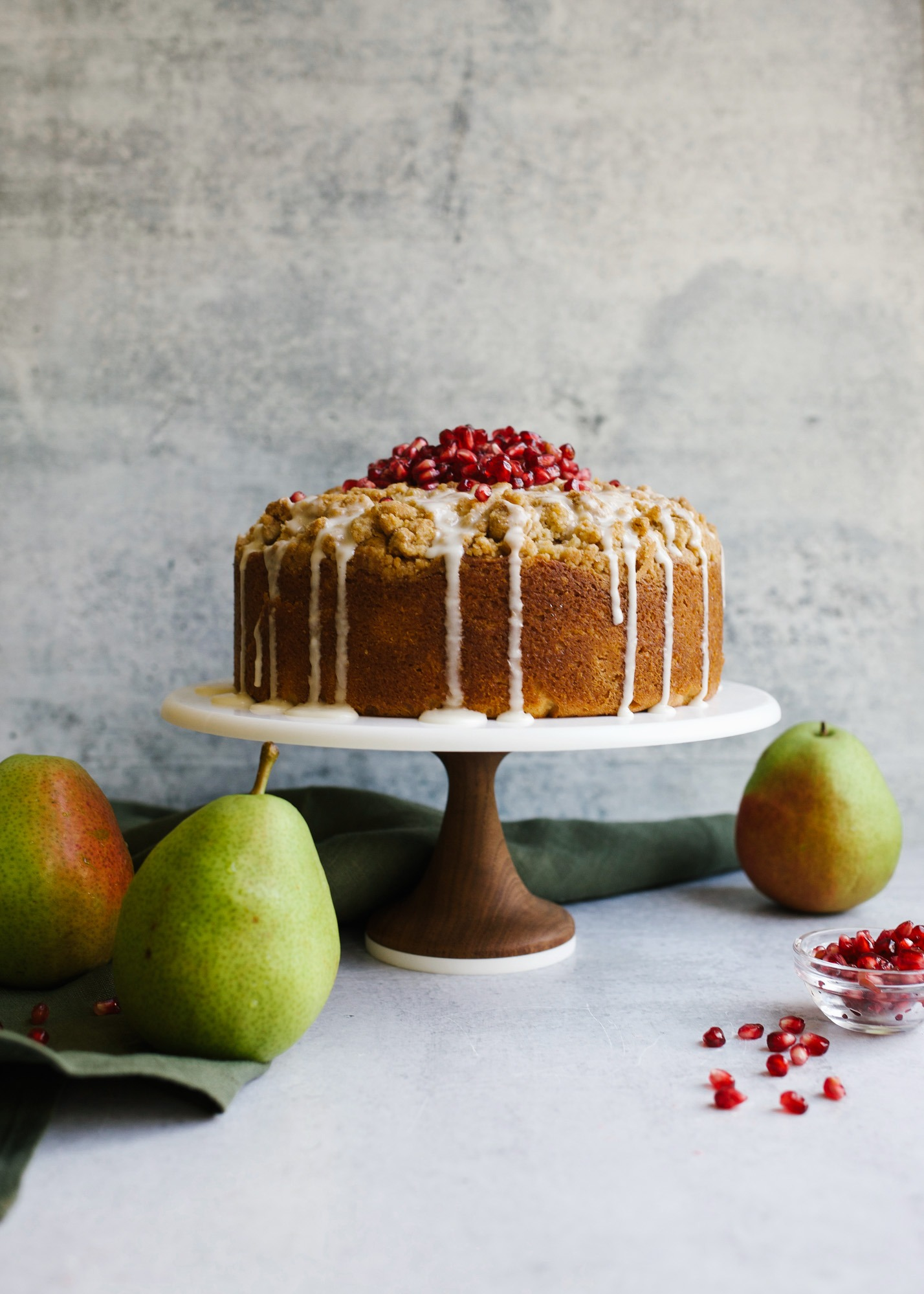 Pear Almond Cake by Wood and Spoon blog by Kate Wood. This is a simple pound cake bundt cake with a streusel crumb topping that is loaded with fresh sweetened pear fruit and almond flavor. The coffee cake makes a great breakfast or dessert treat or snack for your holiday winter tables. Learn more about the recipe and how to prep this simple cake that can be garnished with pomegranate seeds on thewoodandspoon.com