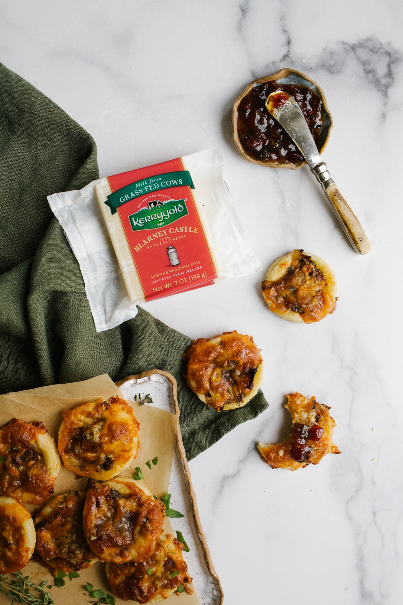 Gouda Cheese Puffs by Wood and Spoon. These are mini round puff pastry appetizers made with caramelized onions, mustard, herbs and shredded gouda cheese. The tarts bake up and are served with a spicy tomato bacon jam. Make these for holiday parties or add to cheese charcuterie and snack boards. Read more about the recipe and get ideas for holiday treats on thewoodandspoon.com