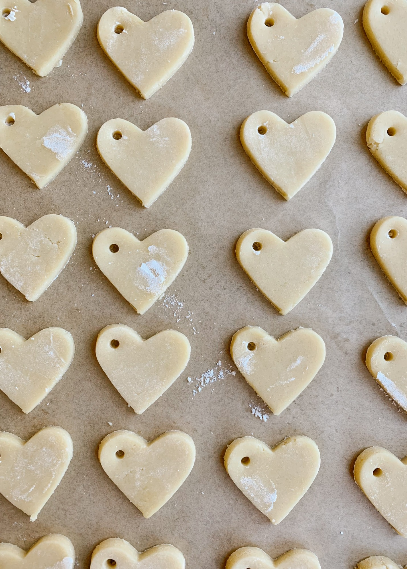 Sugar Cookie Gift Tags by Wood and Spoon blog. Use this tutorial to create, mini frosted iced heart sugar cookies to use as garland, napkin ring holders, gift tags, name tags, necklaces, and more. This simple tutorial gives you the DIY recipe for hard set cookies with homemade icing and ideas for how to use them for Valentine's Day parties, kid crafts, and more. Read about the recipe and how to on thewoodandspoon.com by Kate Wood