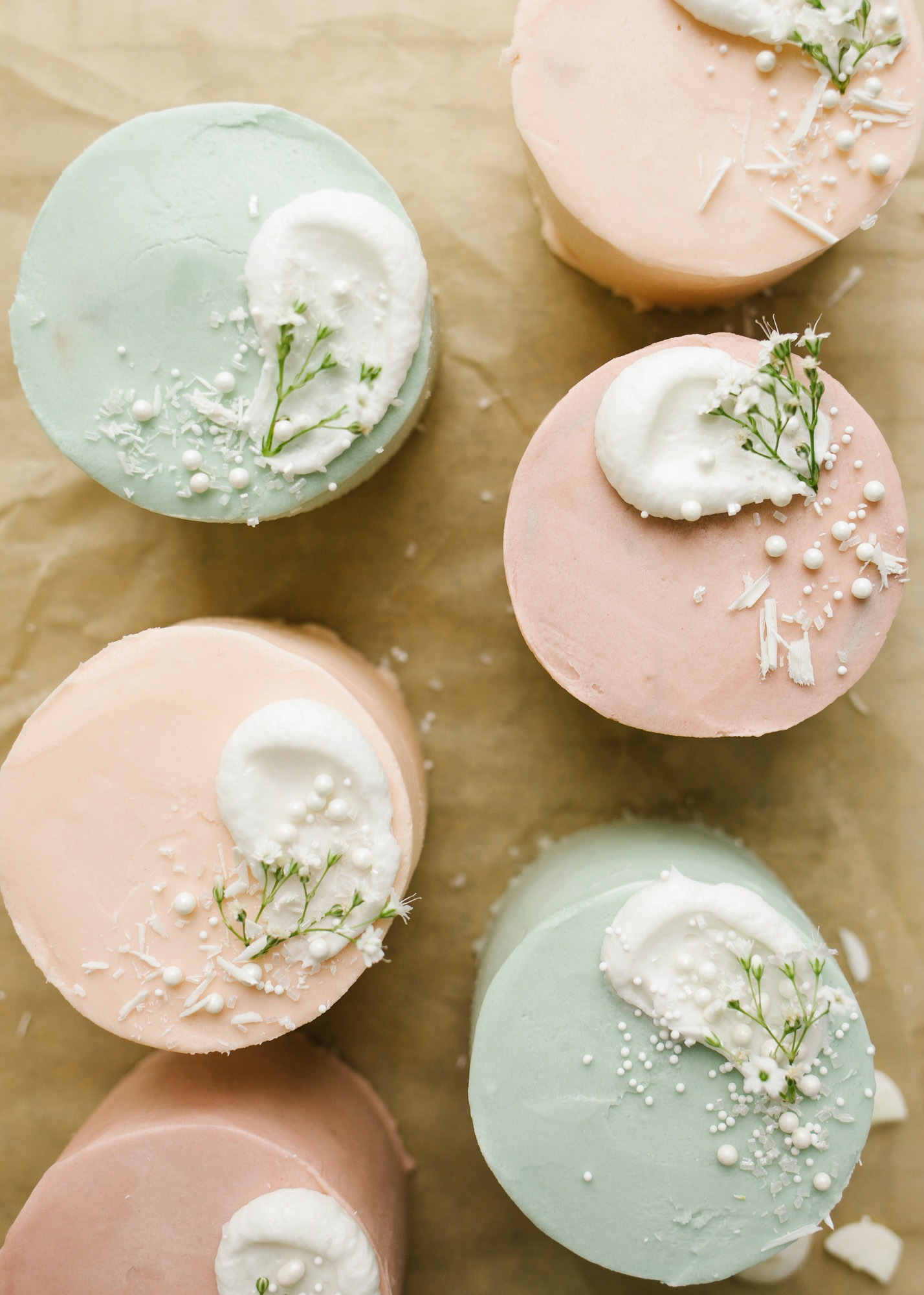 Mini Layer Cakes by Wood and Spoon blog. These are tiny three layer pastel cakes perfect for parties, spring holidays, and Mother's Day. The small vanilla cakes are baked in a sheet pan and then frosted together with a simple American buttercream. The cakes are colored in pale easter colors and served as individual desserts. Perfect mini cake for two. Find the recipe and how to on thewoodandspoon.com by Kate Wood
