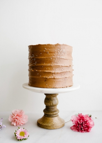 Brownie Batter Cake by Wood and Spoon. This is a fluffy cocoa powder layer cake with espresso and an eggless brownie batter filling and fluffy malt chocolate frosting. The malted chocolate adds a brownie flavor. The cake is moist and flavorful, perfect for chocolate lovers or birthday parties and celebrations. Learn more on the how to for this 3 layer cake on thewoodandspoon.com