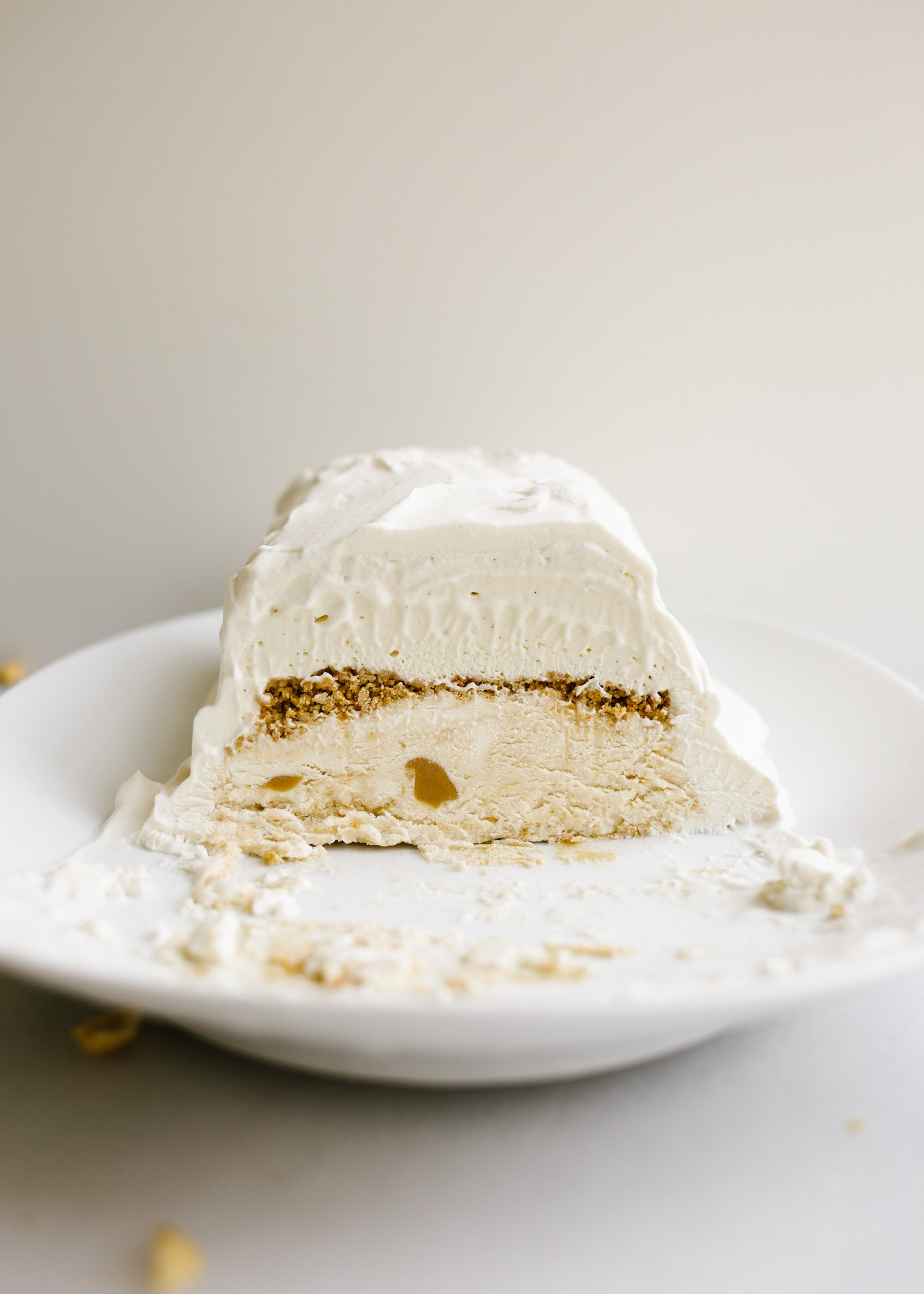 Peanut Butter Honey Graham Ice Cream Cake by Wood and Spoon blog. This is a no-churn ice cream loaf cake with a graham crumble, peanut butter ice cream, honey ice cream, and a swirl of peanut butter throughout The whole thing is topped with whipped cream and cake be made ahead to be served as a simple summer dessert. Learn how to make this homemade ice cream cake here on thewoodandspoon.com