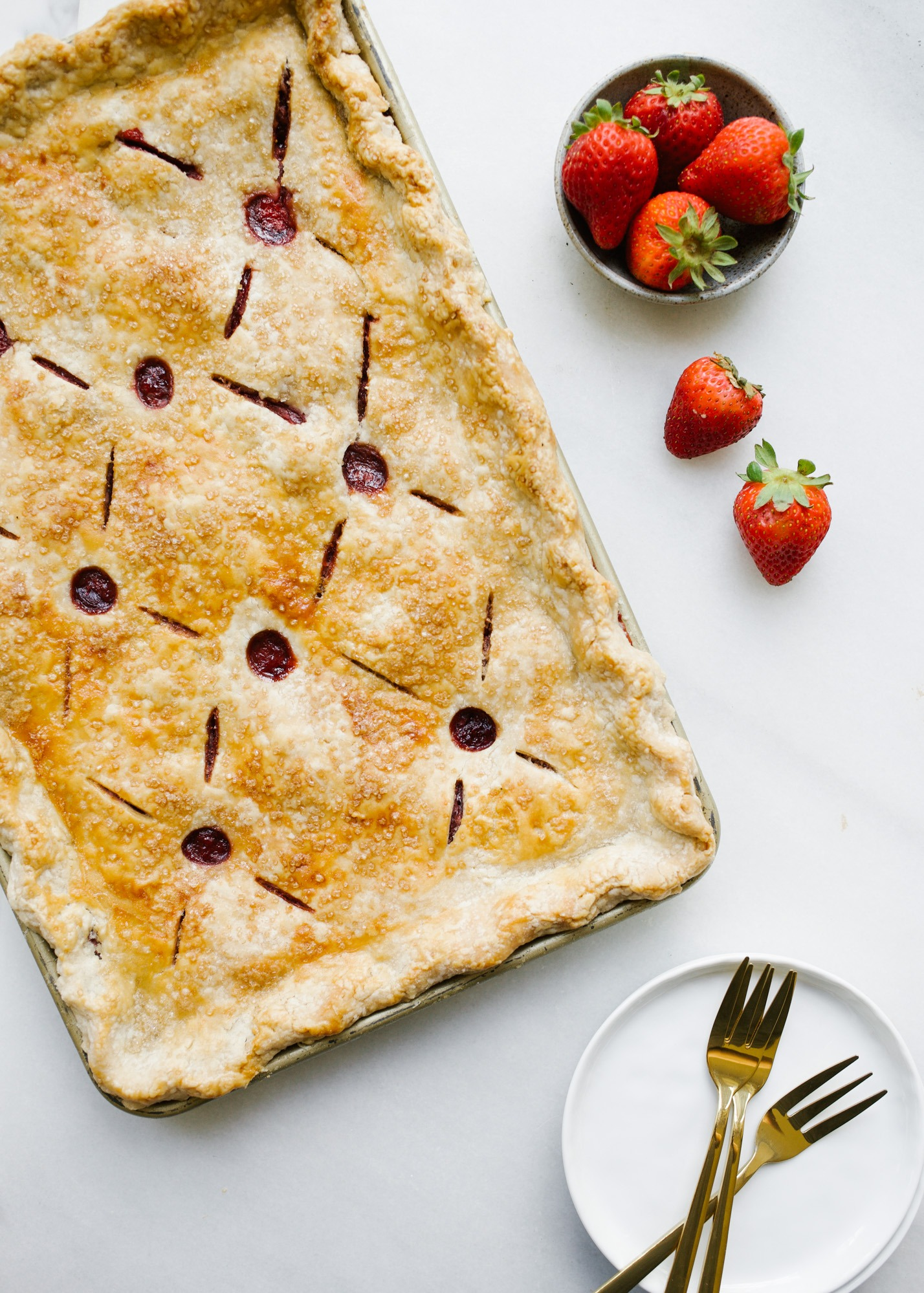 Strawberry Slab Pie by Wood and Spoon. This is a make-ahead feed-a-crowd kind of recipe featuring fresh summer fruit, vanilla, and loads of flaky butter pie crust. This pie ends up being berry pie bars that are easy to serve large groups and almost require no plate or fork. Learn how to make large batch pie with simple homemade filling on thewoodandspoon.com by Kate Wood.