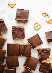 Peanut Butter Cup Bars by Wood and Spoon. These are a simple peanut butter cream stuffed square with a pretzel butter crust and a chocolate topping. These sweet treats make for an easy dessert for fall, tailgates, parties, and more, and are sure to be a favorite for peanut butter lovers. Learn how to make these simple chocolate peanut butter bars on thewoodandspoon.com