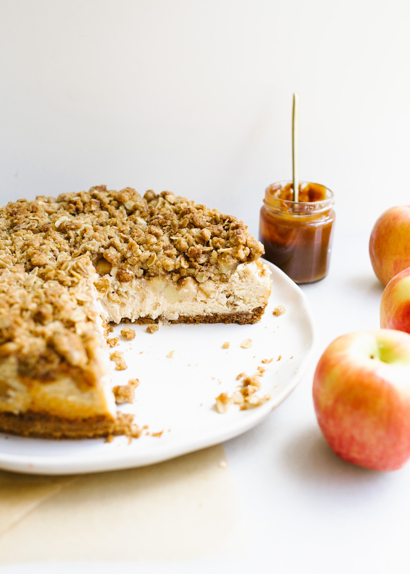Apple Crisp Cheesecake by Wood and Spoon blog. This autumn dessert recipe from Kelsey Siemens features a spiced graham cracker crust, a salted caramel cheesecake filling, fresh apples, and a crumbly brown sugar streusel topping. Served with salted caramel and loads of warm fall flavors, this cake is a terrific make ahead dessert for the holidays including Thanksgiving and Christmas. Learn how to make homemade cheesecake on thewoodandspoon.com