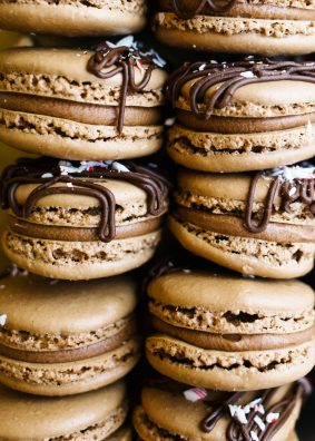 Peppermint Mocha Macarons by Wood and Spoon blog. These are cocoa and coffee scented macarons shells filled with a chocolate peppermint filling and topped with crushed candy canes! These are pretty little treats to celebrate with during the holidays and make a terrific addition to holiday cookie boxes or trays. Learn the ins and outs of making macarons and special holiday Christmas ones at that, on thewoodandspoon.com.