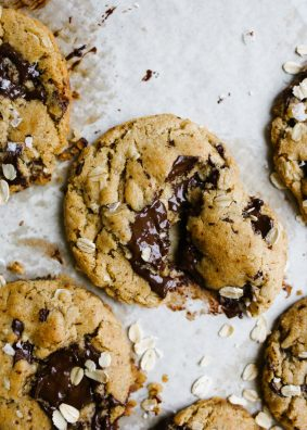 Vegan Peanut Butter Oatmeal Chocolate Chunk Cookies by Wood and Spoon blog. These are simple flax seed egg and coconut oil cookies made with vegan ingredients, creamy peanut butter, oats, and chocolate. The cookies have crisp edges and soft insides and tons of flavor. These healthy cookies taste delicious and are beautiful too! Learn how simple it is to make vegan cookies here on thewoodandspoon.com