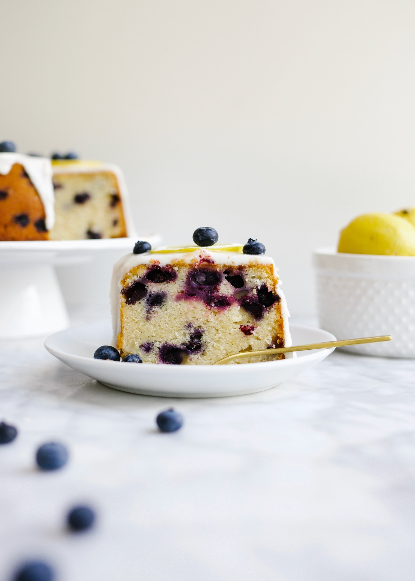 Blueberry Lemon Pound Cake by Wood and Spoon blog. This is a simple buttery pound cake brightened up with the fresh taste of lemon juice and zest and summer blueberries. The cake is iced with a lemon glaze and serves well as a summery breakfast or dessert. Learn how simple it is to make this Southern pound cake on thewoodandspoon.com