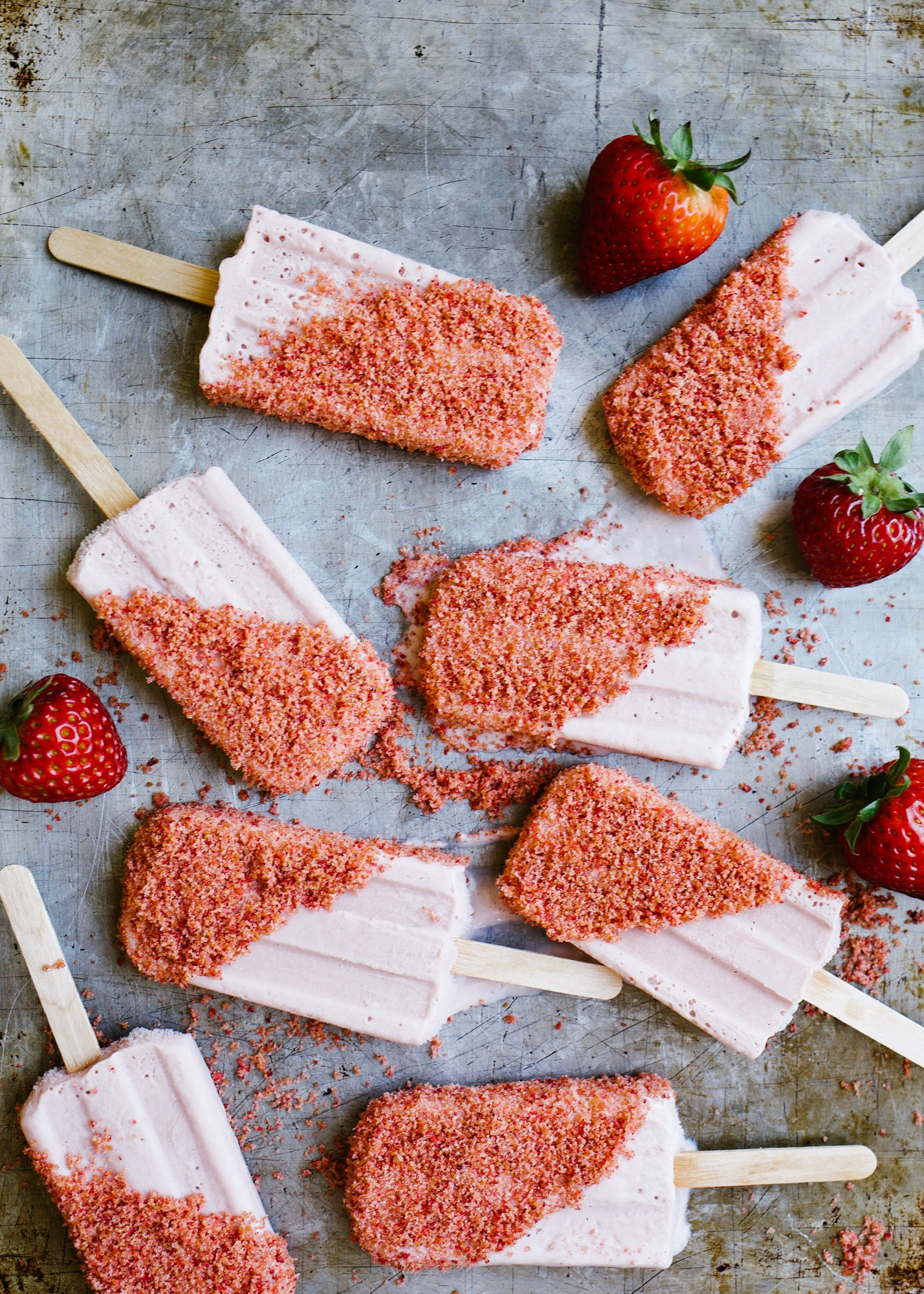 Strawberry Shortcake Popsicles by Wood and Spoon blog. These frozen treats were inspired by the classic novelty treats. A creamy fresh strawberry popsicle is made in a blender and dipped in a freeze-dried strawberry and vanilla cookie butter crumble. The end product is a refreshing and yummy dessert perfect for these summer days. Learn how simple the recipe is on thewoodandspoon.com .